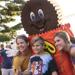 Life-sized Reese's Peanut Butter Cup character smiling for picture with children