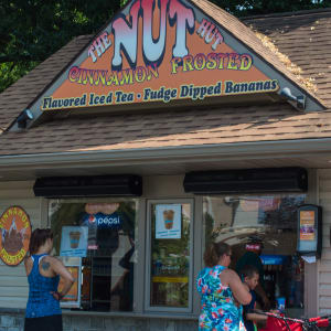 Building with Nut Hut sign on it and two people at the ordering windows