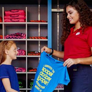 Hersheypark employee selling a SooperDooperLoop tshirt to a little girl and her mom