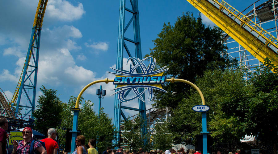 The sign for skyrush roller coaster with a lot of people standing around and the coaster in the back