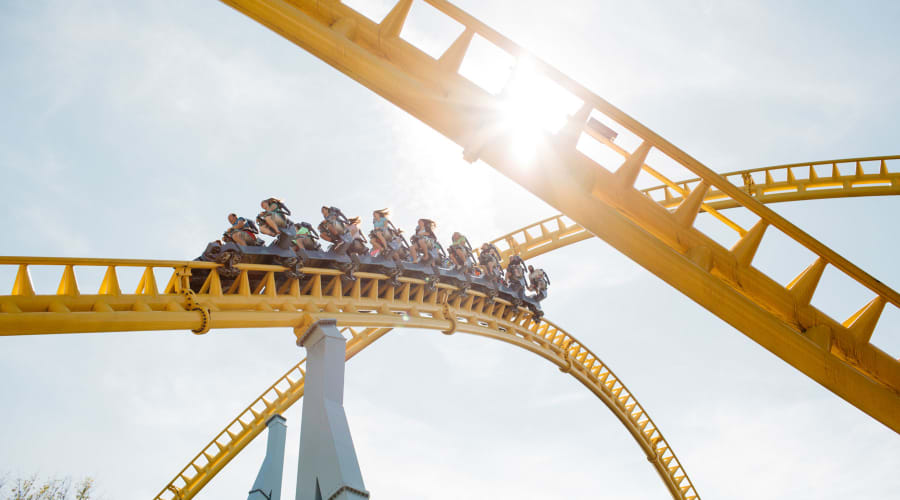 Angle of Skyrush Rollercoaster that captures people riding it and the sun shining from behind