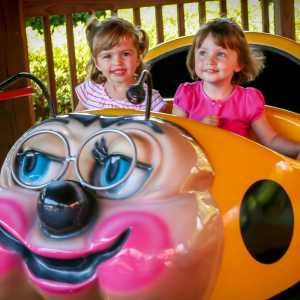 2 adorable littler girls riding the granny bug ride at Hersheypark
