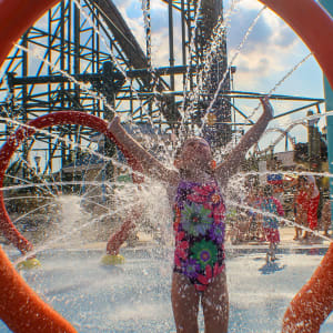 girl getting splashed at shoreline sprayground water attraction