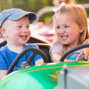 Children Smiling on Traffic Jam ride at Hersheypark as they pretend to drive a car