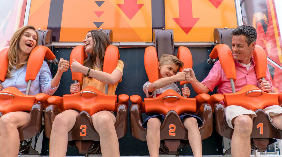 Family of four fist bumping eachother before their ride on Hersheys Triple Tower