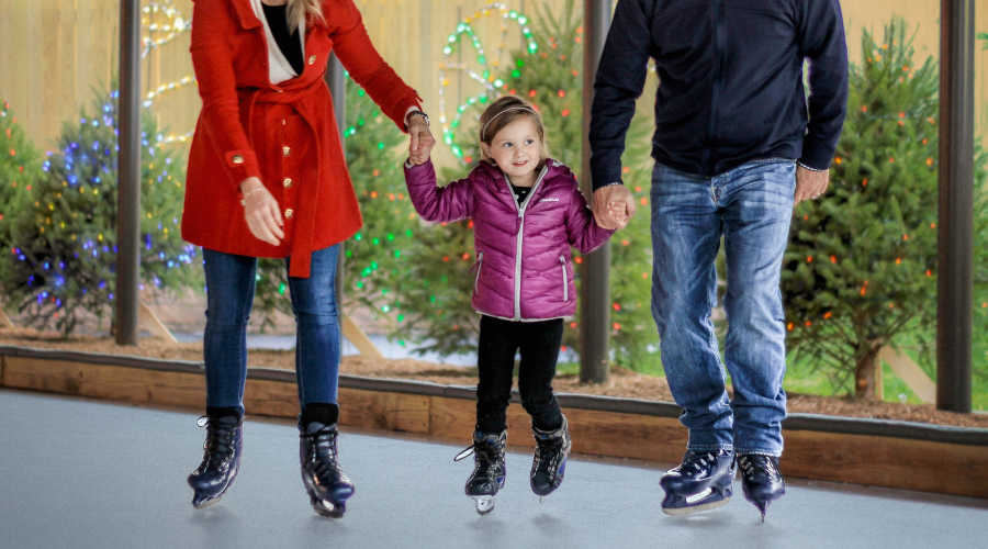 little girl holding her parents hands as she iceskates