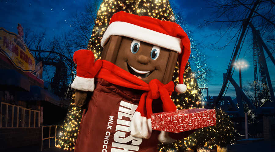 Hersheybar character wearing hat and scarf holding a present and waving
